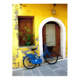 Blue bicycle against a yellow wall post cards