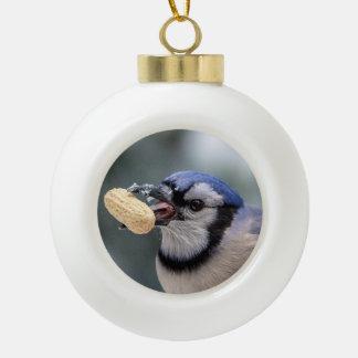 Blue jay with a peanut ceramic ball christmas ornament