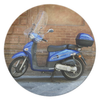 Blue motor scooter by red wall, Siena, Italy Plate