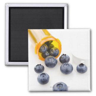 Blueberries spilling from prescription bottle fridge magnet