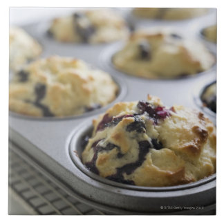 Blueberry muffins in a baking tin on a cooling large square tile