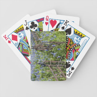 Bluebonnets and phlox surrounding cemetery gate bicycle playing cards