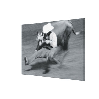 Blurred shot of cowboy wrestling steer canvas print