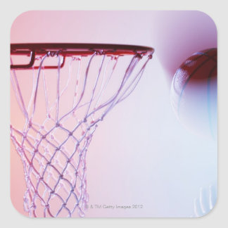 Blurred view of basketball going into hoop square sticker