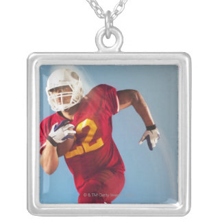 Blurred view of football player running with silver plated necklace