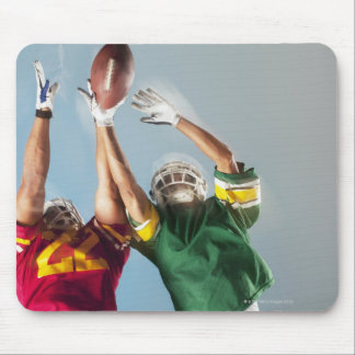 Blurred view of football players reaching for mouse pad