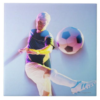 Blurred view of soccer player kicking ball 2 large square tile