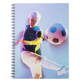 Blurred view of soccer player kicking ball 2 notebooks