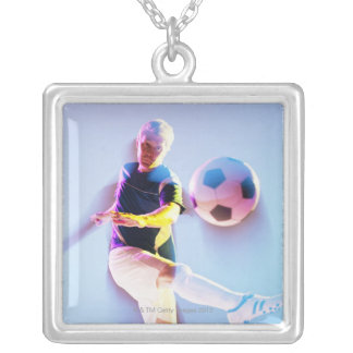 Blurred view of soccer player kicking ball 2 square pendant necklace