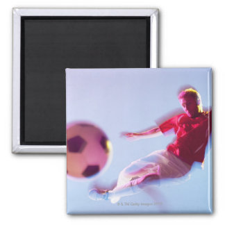 Blurred view of soccer player kicking ball magnet