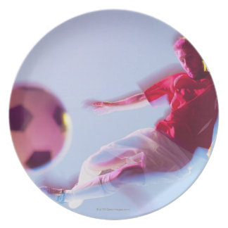 Blurred view of soccer player kicking ball plate