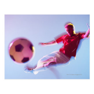 Blurred view of soccer player kicking ball postcard