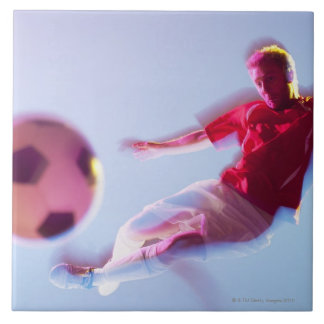 Blurred view of soccer player kicking ball tile