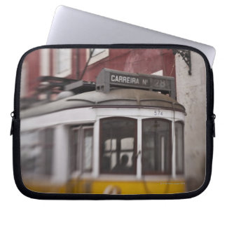 Blurred view of streetcar on city street laptop sleeve
