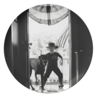 Blurred young boy and dog on porch plate