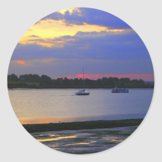 Boats passing on the river at sunset sticker