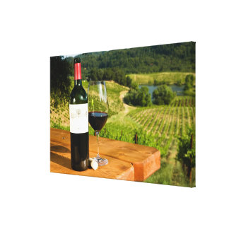 Bottle of red wine and glass on table canvas print