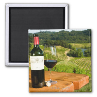 Bottle of red wine and glass on table square magnet