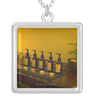 Bottles of aromatherapy oil in the beauty salon, silver plated necklace