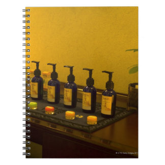 Bottles of aromatherapy oil in the beauty salon, spiral notebook