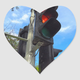 Bottom view on traffic light and road sign closeup heart sticker