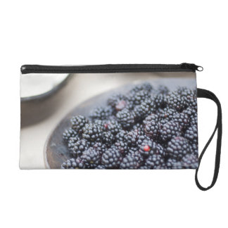 Bowl of blackberries on a table wristlet clutches