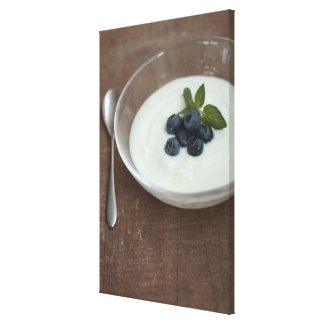 Bowl of yoghurt with blueberry on table canvas print