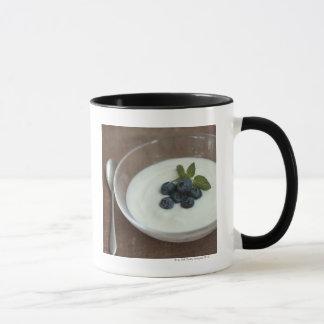 Bowl of yoghurt with blueberry on table mug