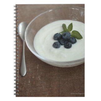 Bowl of yoghurt with blueberry on table notebooks