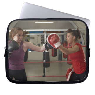 Boxer training with coach in gym computer sleeves