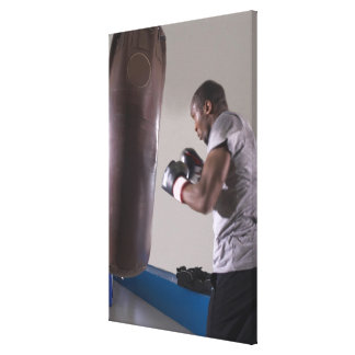 Boxer using punching bag in gym canvas print
