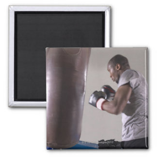 Boxer using punching bag in gym magnet