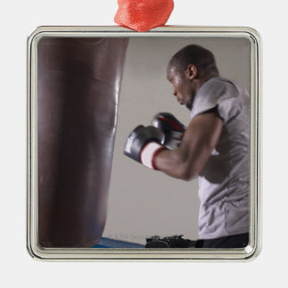 Boxer using punching bag in gym Silver-Colored square decoration