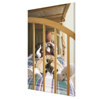 Boy (11-13) lying on bed, playing with canvas print