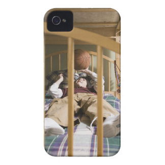 Boy (11-13) lying on bed, playing with iPhone 4 Case-Mate cases