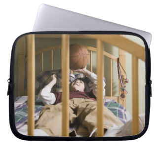 Boy (11-13) lying on bed, playing with laptop sleeve