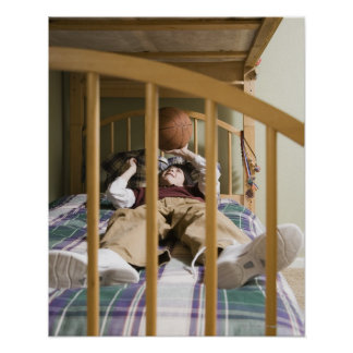 Boy (11-13) lying on bed, playing with poster