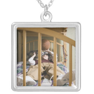 Boy (11-13) lying on bed, playing with silver plated necklace
