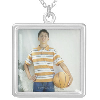 Boy (12-13) standing in front of white square pendant necklace