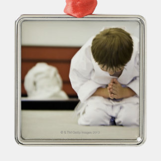 Boy (4-5 years) wearing karate outfit bowing, christmas ornament