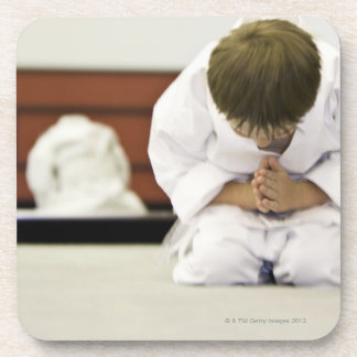 Boy (4-5 years) wearing karate outfit bowing, coaster