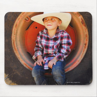 Boy (4-7) yrs old, sitting in tractor tire. mouse mat