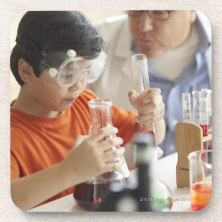 Boy (6-7) and teacher in chemistry class coaster