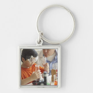 Boy (6-7) and teacher in chemistry class key ring