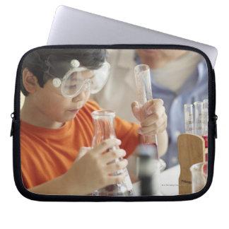 Boy (6-7) and teacher in chemistry class laptop sleeve