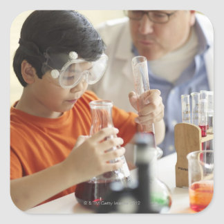 Boy (6-7) and teacher in chemistry class square sticker