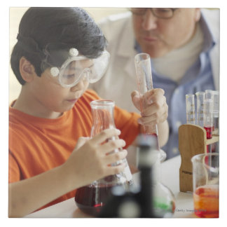 Boy (6-7) and teacher in chemistry class tile