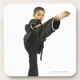 Boy (6-8) in karate outfit kicking drink coaster