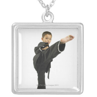 Boy (6-8) in karate outfit kicking square pendant necklace