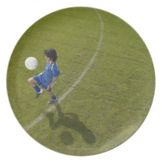 Boy (8-10) footballer practicing skills, plate